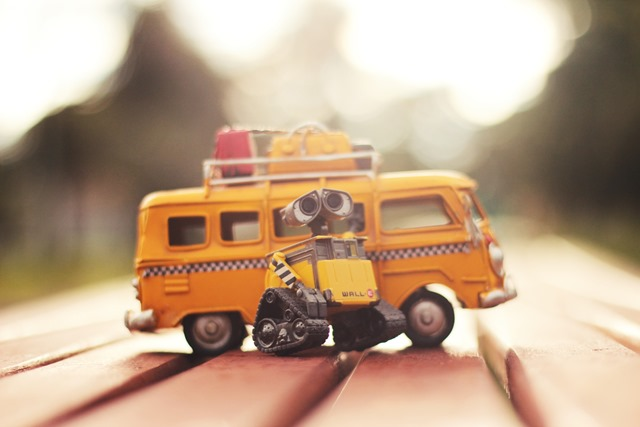 Showing Wall-E infront of a yellow VW bus with taxi stripes